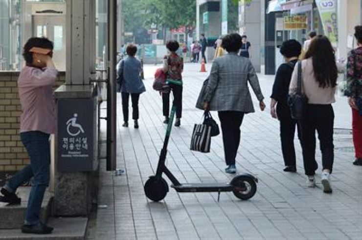 An electric scooter is parked on a sidewalk in front of Seolleung Station in Seoul in this May photo. /Korea Times file