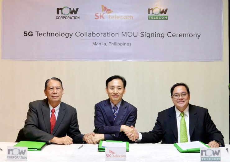 Shim Sang-soo, center, head of infrastructure business at SK Telecom, poses with Thomas Aquino, left, chairman of NOW Corporation, and Mel V. Velarde, chairman of NOW Telecom, after signing an MOU to launch 5G service in the Philippines in Manila, Oct. 24. / Courtesy of SK Telecom