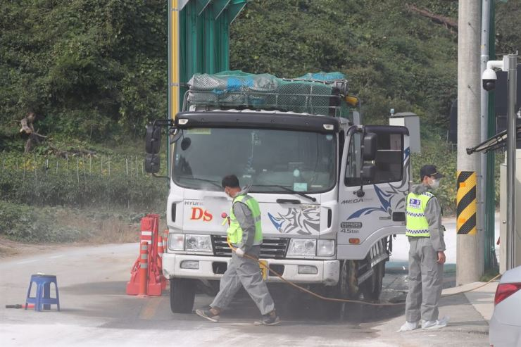 Korean quarantine officials fumigate a vehicle entering a pig farm in Jukseong County in Paju, Gyeonggi Province, Tuesday, where African swine fever was contracted. Yonhap