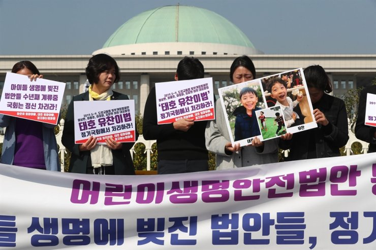 Rep. Lee Jeong-mi of the minor Justice Party, second from left, and parents of children killed in traffic accidents rally in front of the National Assembly on Yeouido in Seoul, Monday, to call on the Assembly to pass pending bills on children's traffic safety. Yonhap