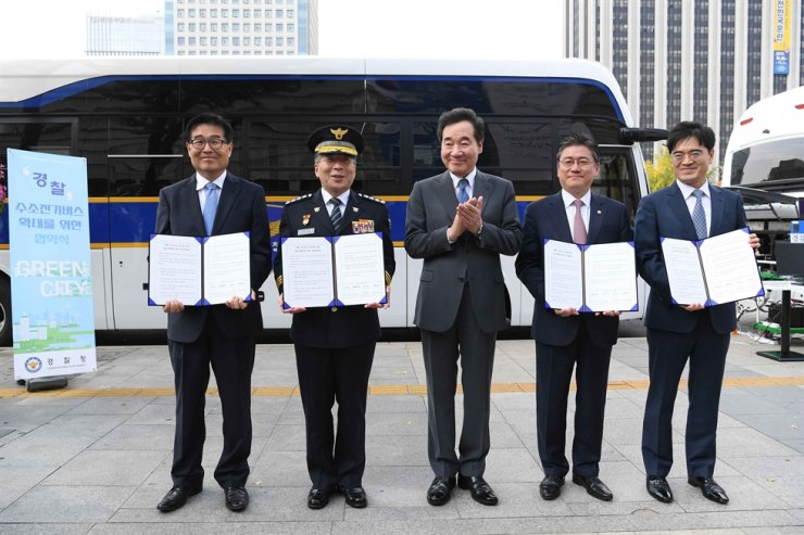 Hyundai Motor President Kong Young-woon, right, poses with Prime Minister Lee Nak-yon, center, and other government officials after signing an MOU for operation of hydrogen-powered police buses at Gwanghwamun, central Seoul, Thursday. / Courtesy of Hyundai Motor