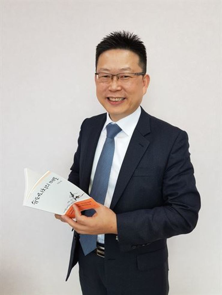 Shin Dong-il, deputy head of KB Kookmin Bank's Gangnam Star private banking center, holds his recently published book, 'Super Rich's Memo,' at his office in southeastern Seoul, Oct. 17. / Korea Times photo by Park Jae-hyuk
