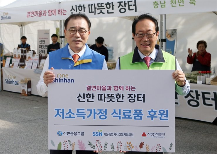 Shinhan Financial Group Chairman Cho Yong-byoung, left, poses with Seoul Council on Social Welfare Chairman Jung Yeon-bo at the financial group's headquarters in Seoul, Thursday. Opening a marketplace for its affiliated villages to sell groceries, Shinhan bought groceries worth 50 million won ($43,000) and donated them to low-income families through the council. / Courtesy of Shinhan Financial Group