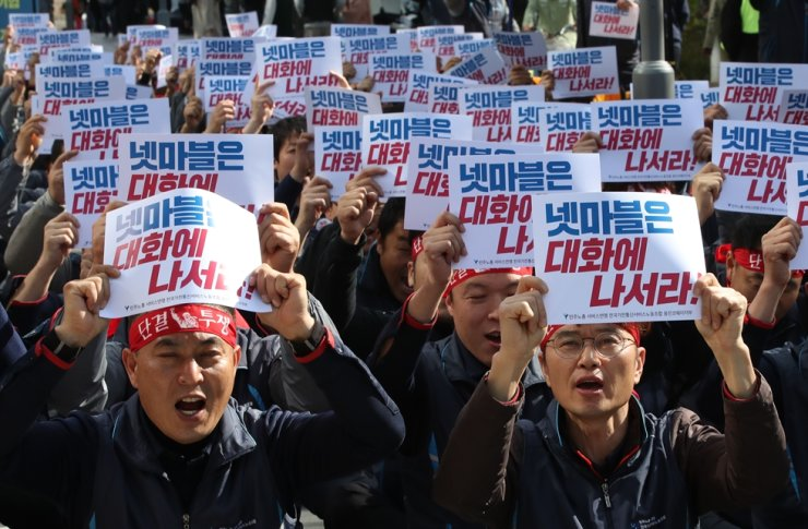 Members of the maintenance workers' union at Woongjin Coway display banners demanding Netmarble have an open discussion and guarantee their job security in front of the company's headquarters in Seoul, Oct. 29. / Yonhap