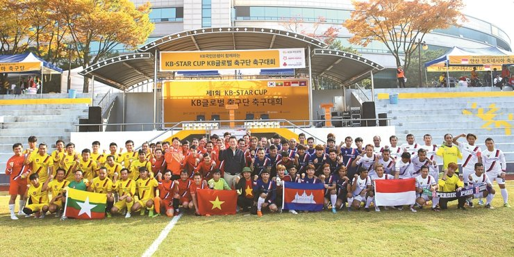 Participants of KB Kookmin Bank's KB Star Cup football competition for foreign workers pose after the event held at the lender's training center in Cheonan, Sunday. This was the first competition, in which four teams representing Cambodia, Myanmar, Indonesia and Vietnam took part. / Courtesy of KB Kookmin Bank