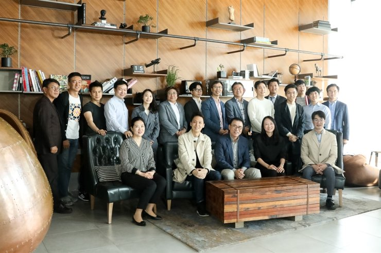 Shinhan Financial Group Chairman Cho Yong-byoung, front row center, poses with startup employees at L7 Hongdae Hotel in Seoul, Tuesday. Shinhan held its Uni-Talk event there to talk with startup owners supported by Shinhan Future's Lab startup accelerator program. / Courtesy of Shinhan Financial Group