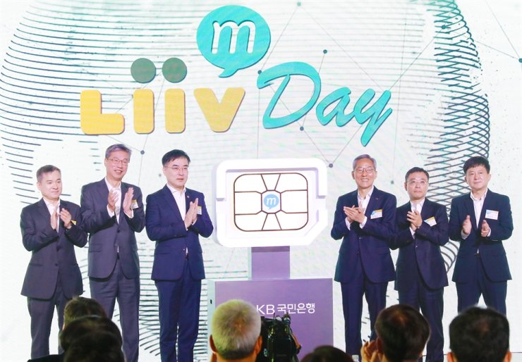 KB Financial Group Chairman Yoon Jong-kyoo, third from right, applauds with KB Kookmin Bank CEO Hur Yin, second from left, and other officials at the bank's event marking its launch of Liiv M, a budget phone service at the Banyan Tree Club & Spa, Monday. First from left is LG Uplus CEO Ha Hyun-hwoi and third from left Financial Services Commission Vice Chairman Sohn Byung-doo. Courtesy of KB Kookmin Bank
