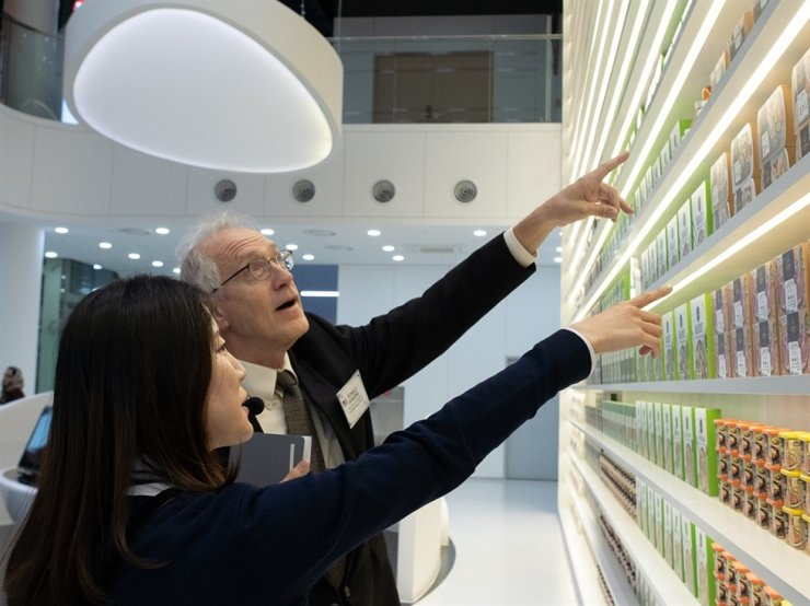 U.S. Embassy in Seoul Agricultural Minister-Counselor Ron Verdonk, right, listens to an explanation from an official on CJ CheilJedang's home meal replacement products at the company's research center in Suwon, Gyeonggi Province, Sunday. Along with Verdonk, CJ CheilJedang invited delegations from seven countries to the research center and introduced Korean food products. Courtesy of CJ CheilJedang