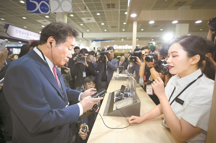 Prime Minister Lee Nak-yeon, left, tries out Samsung Electronics' Galaxy Fold foldable smartphone during the Korea Electronics Show held at COEX in southern Seoul, Tuesday. / Yonhap
