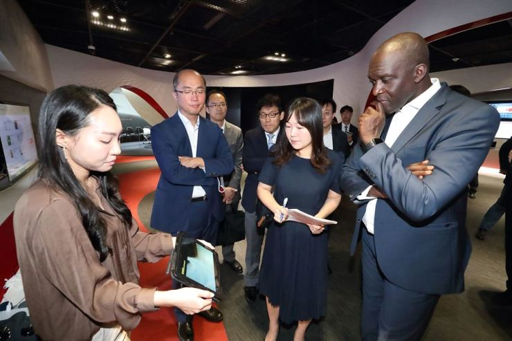 Makhtar Diop, right, the World Bank's vice president for infrastructure, listens to a KT employee's explanation about the Korean firm KT's 5G technologies during his visit to the telecom firm's R&D center in Seoul, Friday. / Courtesy of KT