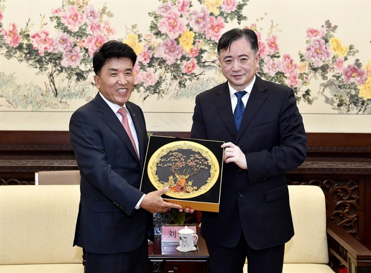 Hana Financial Group Vice Chairman Ham Young-joo, left, poses with Liu Xin, mayor of China's Changchun, after being named an honorary citizen of the city in Jilin Province, at City Hall, Wednesday. Ham was recognized for his contributions to the financial development of the city. / Courtesy of Hana Financial Group