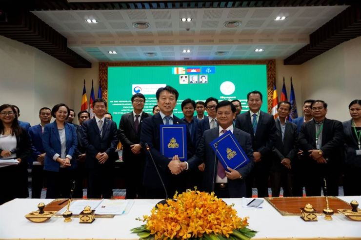 Public Procurement Service Administrator Jung Moo-kyung, front row left, holds his copy of a signed memorandum of understanding while shaking hands with his Cambodian counterpart at the finance ministry of Phnom Penh, Oct. 2 (local time). Under the agreement, Korea will help the Southeast Asian country adopt its e-procurement system, the Korea ONline E-Procurement System (KONEPS). Courtesy of Public Procurement Service