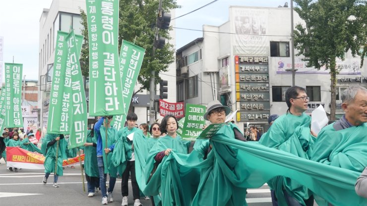 Protesters against the government's construction plan for a second airport on Jeju Island parade from Cheong Wa Dae to Sejongno Park in Seoul's Jongno-gu, Oct. 16, holding green banners that symbolize peace. Courtesy of Korea Federation for Environmental Movements