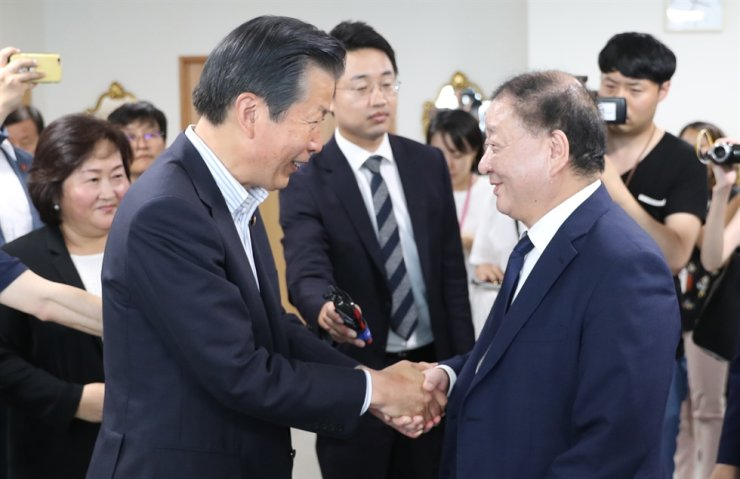 Rep. Kang Chang-il of the ruling Democratic Party of Korea, right, who heads the South Korea-Japan Parliamentarians' Union, shakes hands with Natsuo Yamaguchi, chief representative of Japan's Komeito party, a coalition partner of Japan's ruling Liberal Democratic Party, at the Komeito party headquarters in Tokyo on July 31, ahead of their meeting to discuss the Seoul-Tokyo trade row. Yonhap