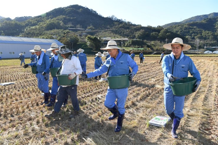 POSCO Chairman Choi Jeong-woo, second from right, and employees use the steelmaking byproduct slag, which has been processed to make fertilizer, in paddy fields in Gwangyang, South Jeolla Province, Wednesday. Courtesy of POSCO