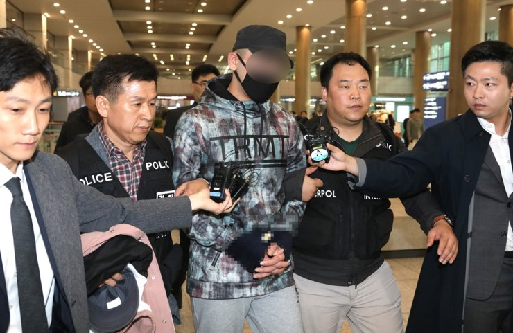 Police detain a Kazakh man at Incheon International Airport, Monday, after he was extradited for alleged involvement in a hit-run accident that seriously injured a boy. Yonhap