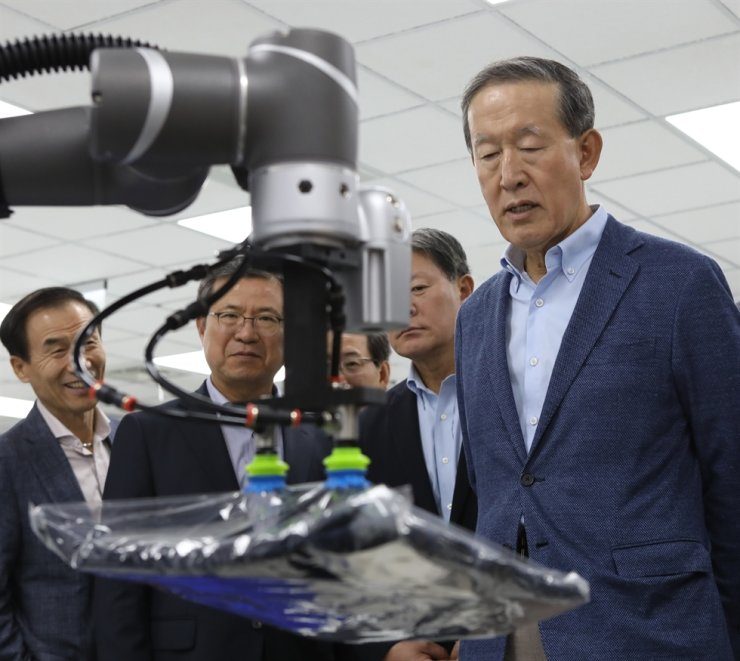 GS Group Chairman Huh Chang-soo, right, is briefed on Techman Robot's industrial robots during his visit to the Taiwan-based robotics company, Thursday. / Courtesy of GS Group
