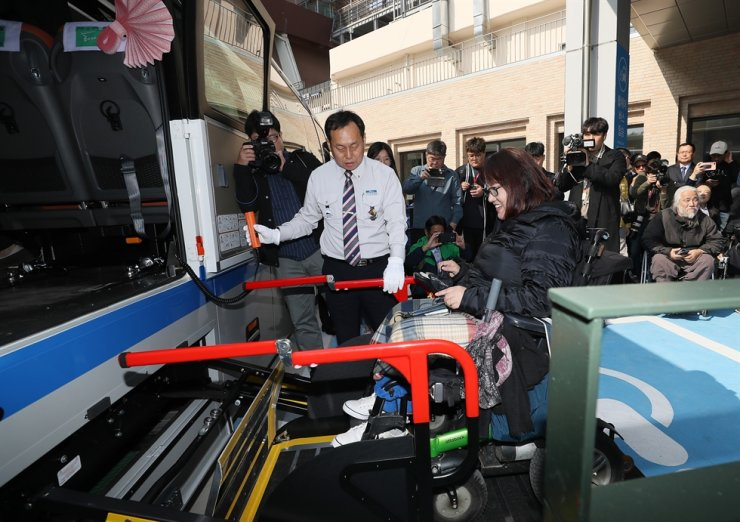 A wheelchair user boards an inter-city bus, which has been equipped with space for wheelchairs on board, and equipment for wheelchair users to board and exit the bus, at Seoul Express Bus Terminal in southern Seoul, Monday. After repeated requests from disabled rights groups, bus companies agreed to test run 10 such special buses on routes between Seoul and the cities of Busan, Gangneung, Jeonju and Dangjin. / Yonhap