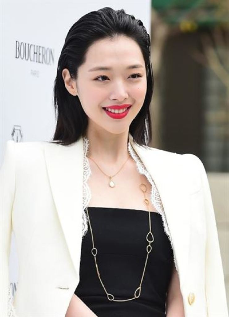 Sulli smiles in front of a photo wall. Korea times file