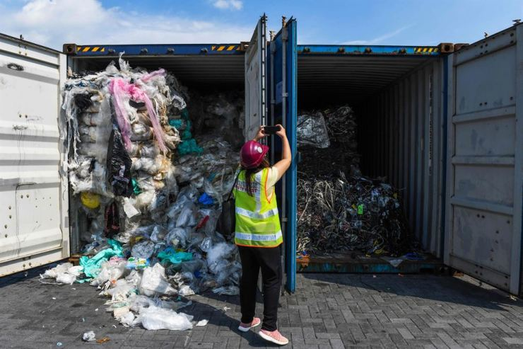 A Malaysian government official checks containers imported from Korea that were filled with garbage. Korea exported the containers as recyclable plastic waste. Korea Times file
