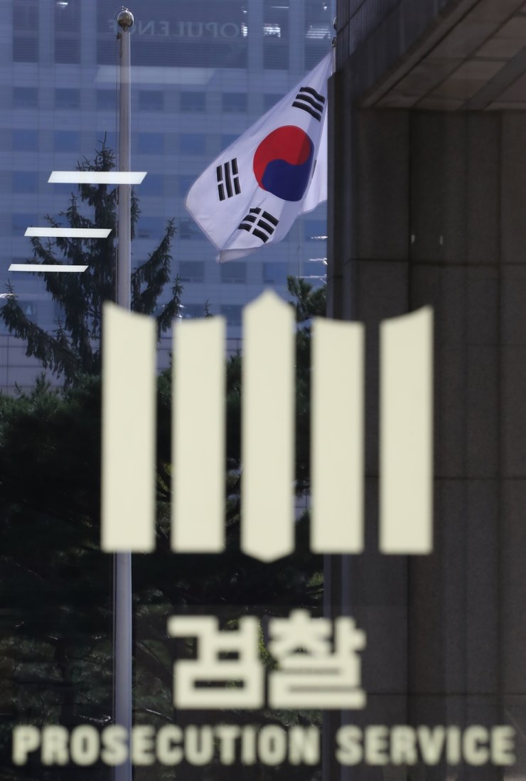 The Korean national flag is reflected on the main door of the Seoul Central District Prosecutors' Office in Seoul, Monday. The prosecution requested a Seoul court to issue an arrest warrant for former Justice Minister Cho Kuk's wife Chung Kyung-sim over multiple corruption allegations. Yonhap
