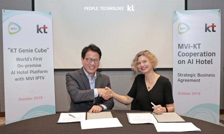 Bae Cheol-gi, left, a senior vice president who is charge of global business development at KT, shakes hands with MVI CEO Anke Gill at Kuala Lumpur, Friday, during a signing ceremony for their business cooperation on AI hotel services. / Courtesy of KT