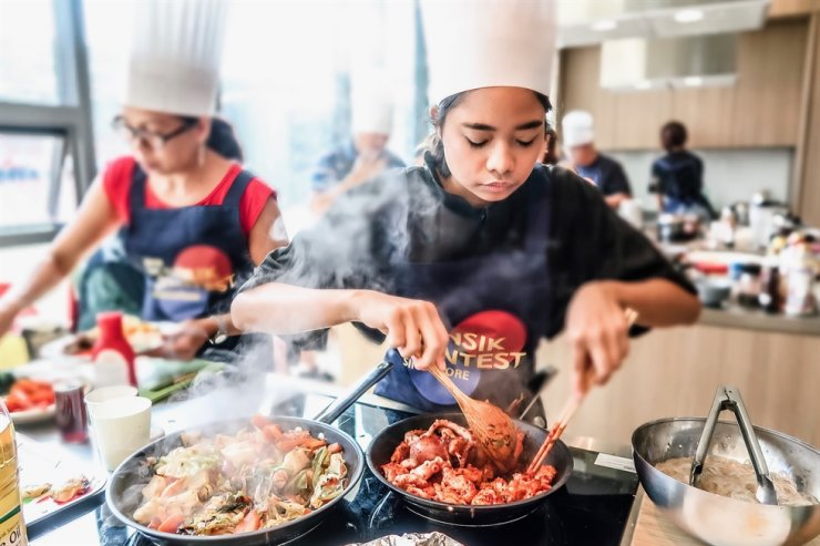 Participants in a preliminary round of the 'hansik' (Korean cuisine) contest in Singapore cook food in this July photo. Winners of the preliminary round in eight ASEAN countries will come to Korea for the ASEAN-Korea Final Hansik Contest to be held in Seoul, Nov. 26. / Courtesy of Korean Food Promotion Institute