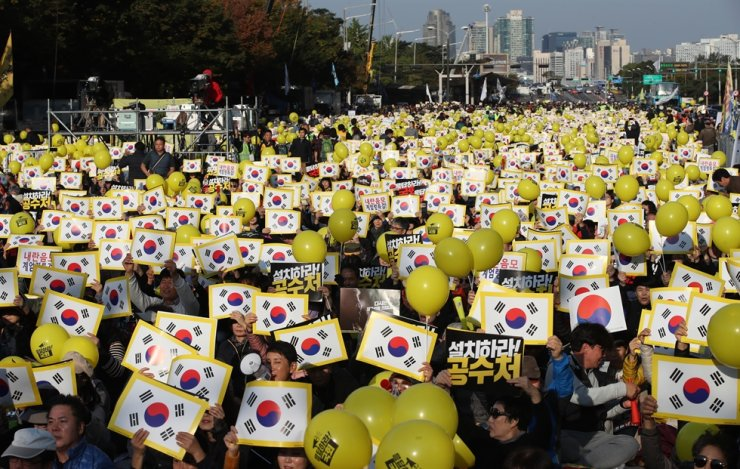 Protesters hold up national flags and yellow balloons at a rally calling for prosecutorial reform next to Yeouido Park, Seoul, Saturday. / Yonhap