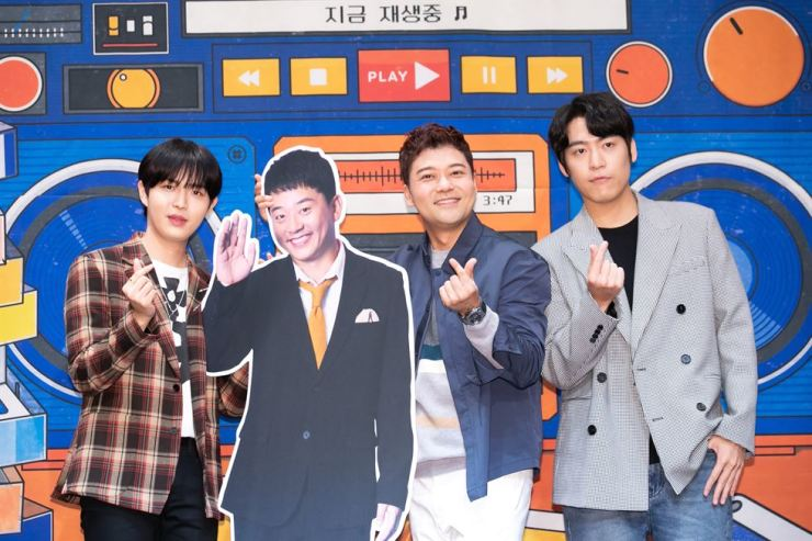 From left, Kim Jae-hwan, Kim Jun-ho ― represented by a cardboard cutout― Jun Hyun-moo, and John Park pose during a news conference for tvN's new music show 'Wednesday Music Playlist 1' at the Ramada Hotel by Wyndham Seoul in Sindorim, Wednesday. Kim Jun-ho couldn't make the press conference that day. / Courtesy of CJ ENM