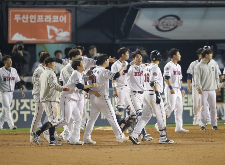 The Doosan Bears players celebrate their first victory against the Kiwoom Heroes 7-6 in the Korean baseball championship series at Jjamsil Stadium in Seoul, Tuesday. /Yonhap
