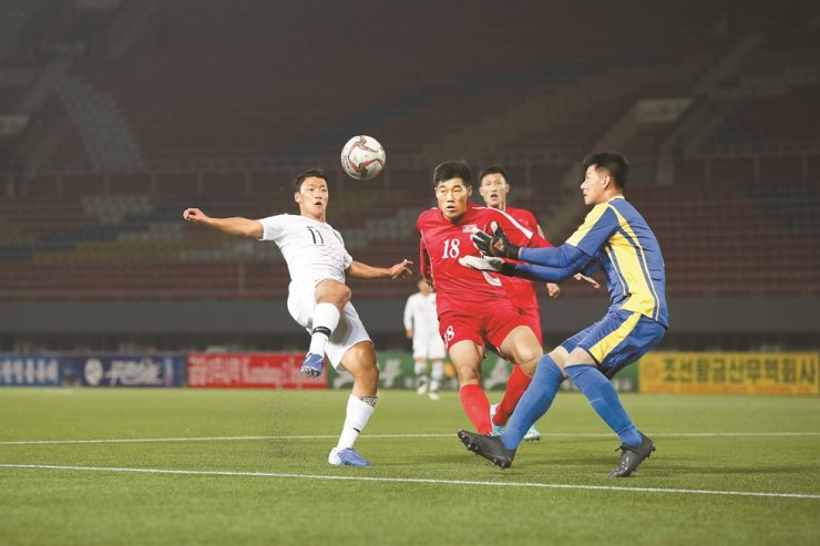 South Korea's Hwang Hee-chan, left, attempts a shot during the 2022 World Cup qualifying match against North Korea at the Kim Il Sung Stadium in Pyongyang, Tuesday. Yonhap