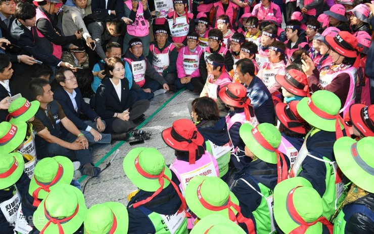 Education Minister Yoo Eun-hae talks with members of the non-regular school workers' union, Tuesday, on a street near Cheong Wa Dae, where they have staged rallies demanding a wage increase. The education authorities and the union agreed to raise basic pay by 1.8 percent and transport allowance by 40,000 won. Following the agreement, the union scrapped its plan to stage a strike from Thursday to Friday. / Korea Times photo by Bae Woo-han