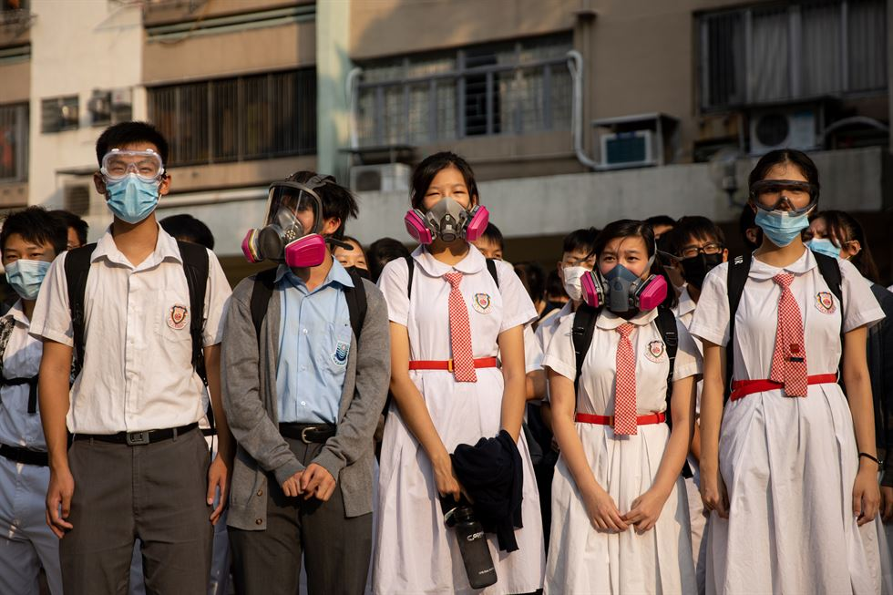 Protesters and students stand outside the Tsuen Wan Public Ho Chuen Yiu Memorial College during a demonstration held to show solidarity with an injured student, in Hong Kong, China, Oct. 2. EPA-Yonhap