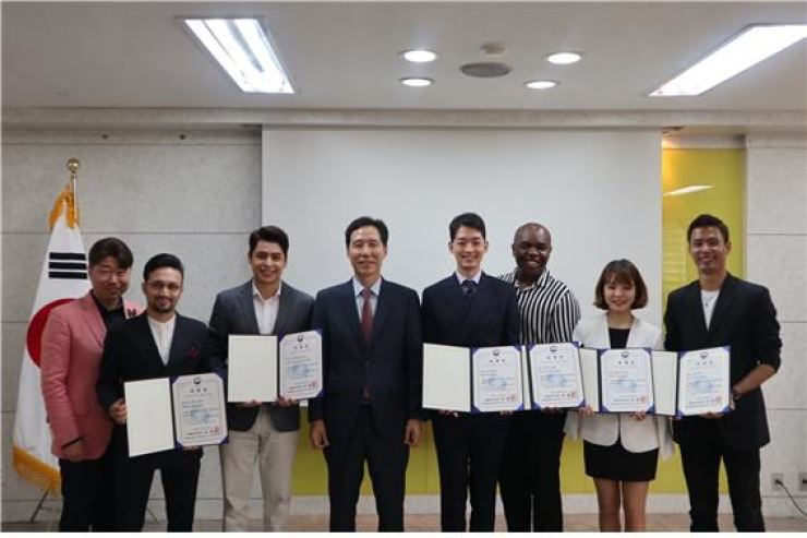 Lee Seung-taek, CEO of the Creative Convergence of FMG Entertainment (left); Zahid Hussain, Christian Burgos; Seoul Immigration Office head Son Hong-ki; Oogi Hitoshi, Terris Brown, Fujimoto Saori and Shakya Sujan Ratna during the Seoul Immigration Office's appointment ceremony at its headquarter in Yangcheon-gu, Seoul, Monday. Courtesy of FMG Entertainment
