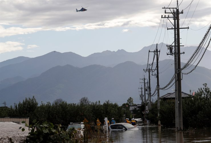 A rescue helicopter flies over rescue workers searching a flooded area in the aftermath of Typhoon Hagibis, which caused severe floods at the Chikuma River in Nagano, Nagano Prefecture, Japan, October 14, 2019. Reuters-Yonhap