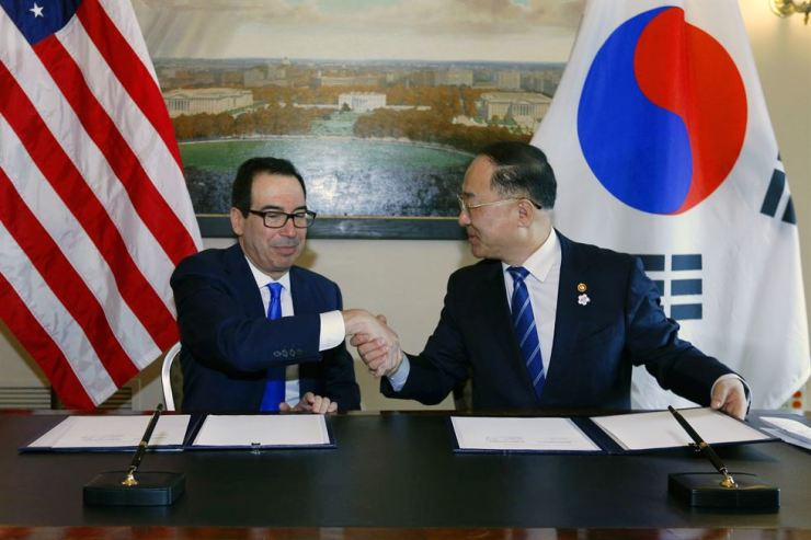 South Korean Finance Minister Hong Nam-ki, right, and U.S. Treasury Secretary Steven Mnuchin sign a memorandum of understanding at the U.S. Treasury Office in Washington, Oct. 17. Yonhap