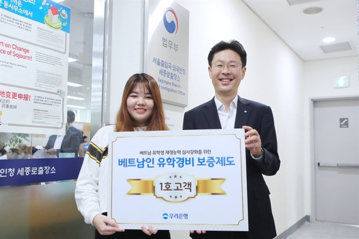 Vo Ngoc Anh Thu, left, the first Vietnamese student who satisfied the tightened visa requirements that came into effect Oct. 1, poses with a Woori Bank employee at Seoul Global Center in downtown Seoul, Sept. 27. The new rule requires Vietnamese students to deposit at least $10,000 into a Korean commercial bank account that allows withdrawal of 5 million won ($4,400) every six months. Woori said Wednesday she selected the bank to follow the new rule which aims to prevent illegal foreign students from overstaying their visas. / Courtesy of Woori Bank