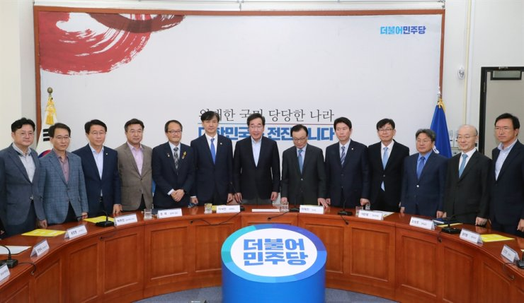 Justice Minister Cho Kuk, sixth from left, Prime Minister Lee Nak-yon, seventh from left, ruling Democratic Party of Korea (DPK) Chairman Rep. Lee Hae-chan, sixth from right, Cheong Wa Dae chief policy secretary Kim Sang-jo, fourth from right, and senior officials of Cheong Wa Dae, the government and the DPK take a group photo before participating in a tripartite meeting between the three bodies to discuss ways to seek prosecution reform at the National Assembly, Sunday. Yonhap