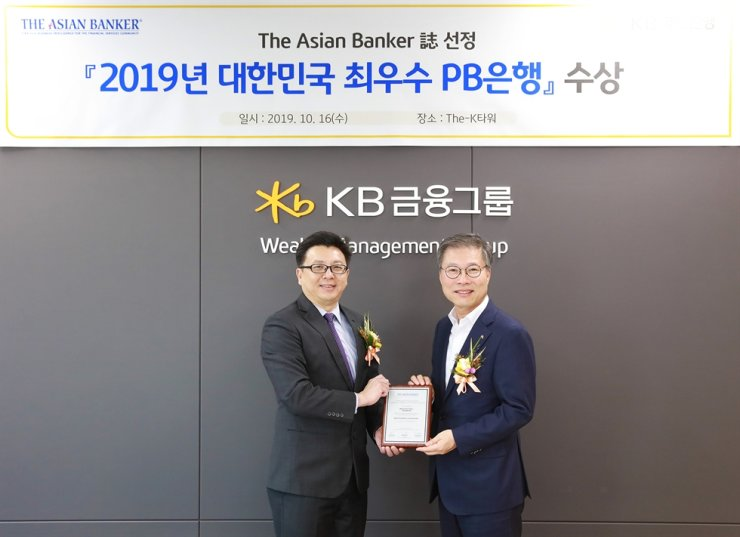 KB Kookmin Bank Wealth Management Group head Kim Young-gil, right, receives an award from Asian Banker managing editor Boon Ping Foo at The-K Tower in Seoul, Wednesday. The Singapore-based journal specializing in the financial services industry selected KB as Korea's best private bank. The bank was also awarded for its trust and pension products. / Courtesy of KB Kookmin Bank