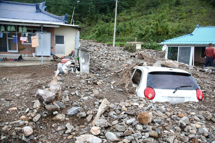 A car is buried in a pile of sand and stones at Uljin, North Gyeongsang Province, Thursday, after Typhoon Mitag struck the area. Yonhap
