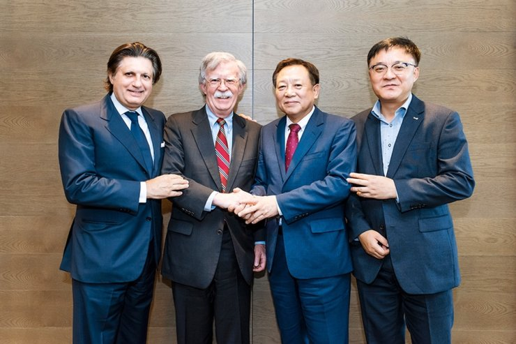 Rhone Group senior adviser John Bolton, second from left, shakes hands with Korea Teachers' Credit Union (KTCU) Chairman Cha Sung-soo, second from right, at The-K Tower in Seoul, Thursday. Left is Rhone Group co-founder Robert Agostinelli. / Courtesy of KTCU