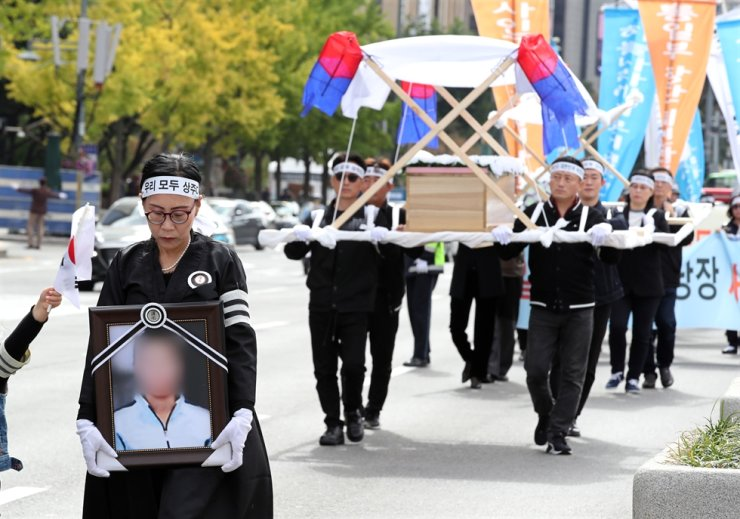 Civic group members hold a mock funeral on a street near Gwanghwamun Square, Seoul, Friday, to call for government action to prevent similar cases to one in which a woman and her son, who defected from North Korea, were found dead in their apartment in July, two months after they died presumably of starvation. /Yonhap