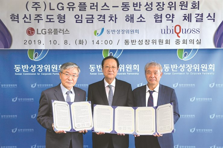 LG Uplus Vice President Lee Hyuk-ju, left, poses with Lee Sang-keun, right, CEO of local network equipment maker Ubiquoss and Kwon Ki-hong, chairman of the Korea Commission for Corporate Partnership (KCCP) after signing an agreement to spend 222.2 billion won ($185 million) to help its subcontractors at the KCCP office in Seoul, Tuesday. / Courtesy of LG Uplus
