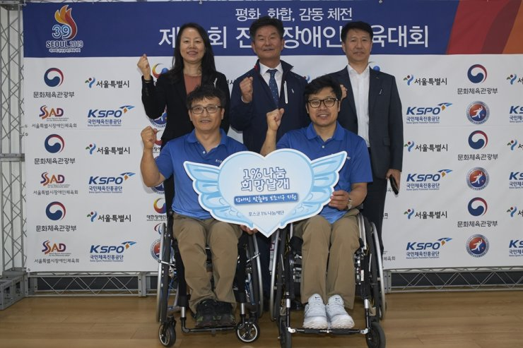 POSCO Corporate Citizenship Office Group Leader Bang Mi-joung, top left, and South Jeolla Province Sports Association for the Disabled Executive Vice President Nam Baek-won, top center, pose with para-bowling athletes after the company's POSCO 1% Foundation donated sports wheelchairs to the athletes on the sidelines of the 39th National Para Games at Jamsil Sports Complex in Seoul, Wednesday. Courtesy of POSCO