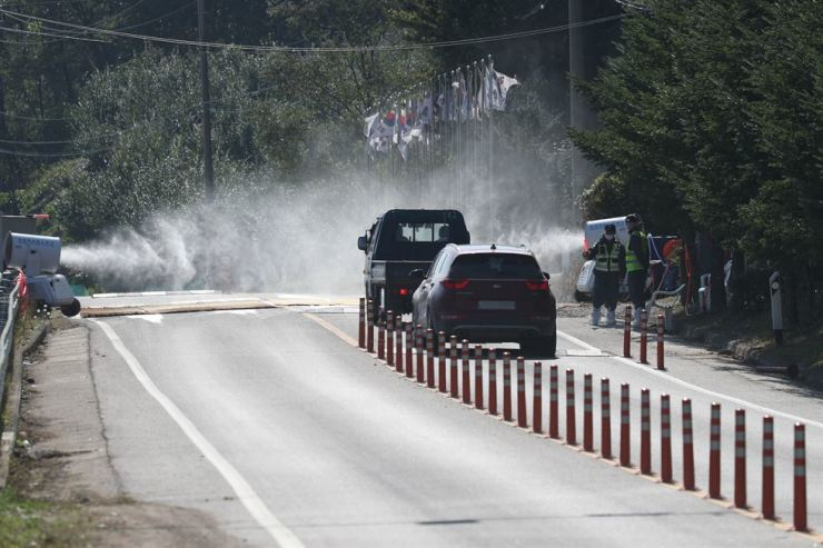 Staff of the Animal and Plant Quarantine Agency, who have been battling the spread of African swine fever for weeks, fumigate vehicles on the road bordering Gyeonggi Province's Yeoncheon and Cheorwon counties. Yeoncheon is one of the regions where the disease has been confirmed. Yonhap