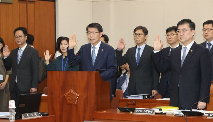 Financial Services Commission Chairman Eun Sung-soo, third from left, takes an oath by a witness before the National Assembly audit in Seoul, Friday. / Yonhap