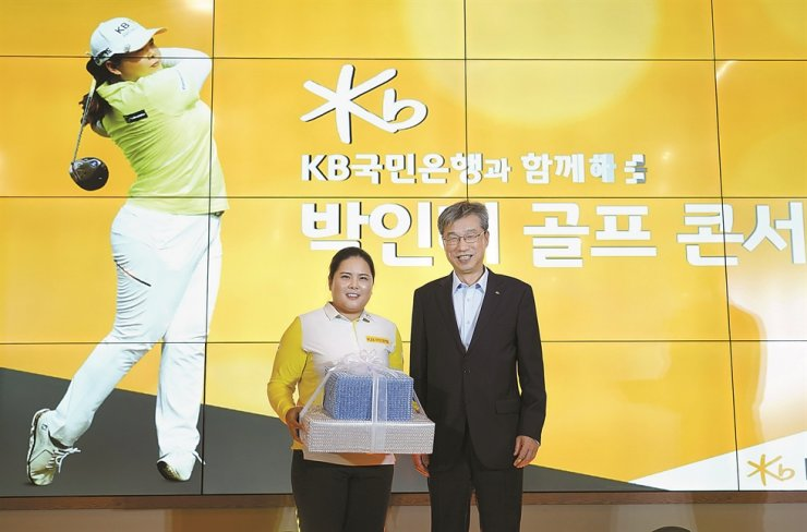 KB Kookmin Bank CEO Hur Yin, right, poses after handing a gift and handwritten card to golfer Park Inbee at the lender's 'Golf Concert' event at the Woo Jeong Hills Country Club in Cheonan, South Chungcheong Province, Friday. KB's VIP customers met with the golfer and learned golf tips at the event. / Courtesy of KB Kookmin Bank