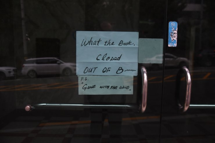 A sign at the front entrance of What the Book? announces the closure of the bookstore. / Korea Times photo by Jon Dunbar