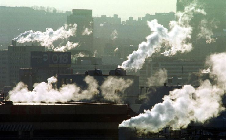 Sub-zero temperature in the morning makes smokes from heating in buildings in Seoul more visible. Korea Times file