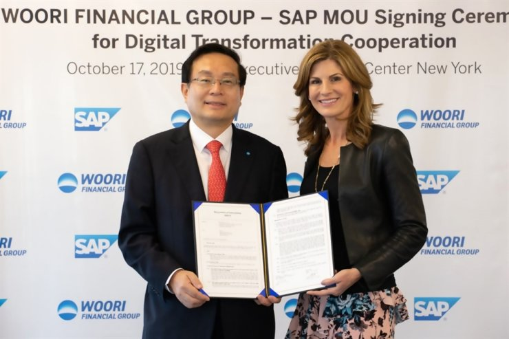 Woori Financial Group Chairman Sohn Tae-seung, left, holds a memorandum of understanding (MOU) with SAP CEO Jennifer Morgan at the SAP Executive Briefing Center in New York, Thursday (local time). The two companies signed the MOU to cooperate in the digital transformation of corporate financing. / Courtesy of Woori Financial Group